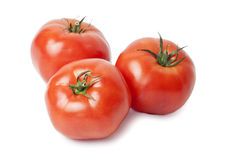 Tomatoes. Three juicy, red tomatoes isolated on white background stock images