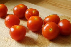 Tomatoes. A few of tomatoes on a wooden plate side by side Royalty Free Stock Image