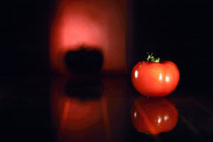 Tomatoes. Juice red tomato reflected on black shiny surface to form double image with red glow and reflection in background Stock Photo