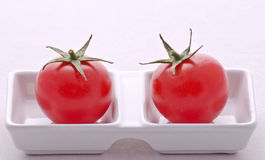Tomatoes. Two red and fresh tomatoes on a kitchen plate Stock Image