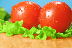 Tomatoes. And lettuce on the cutting board royalty free stock photo