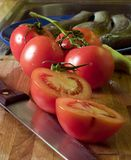 Tomatoes. And knife at cutting board, trouts at background Stock Photos