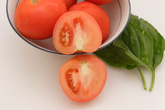 Tomatoes. A bowl with tomatoes and a few leaves of basil Stock Images