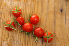 Tomatoes. Cherry tomatoes with water drops   on the pine board Stock Photos