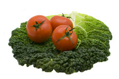 Tomatoes. Three tomatoes on cabbage sheet isolated on the white Stock Images