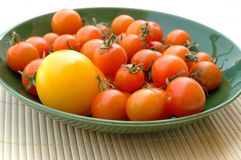 Tomatoes. Bowl of orange cherry tomatoes and one yellow tomato Royalty Free Stock Image