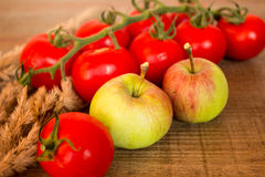 Tomatoes and apples. Picture of tomatoes and apples with grass on a wooden background Stock Image