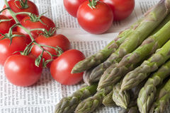 Tomatoes and Asparagus. Shoots on a newspaper royalty free stock photography