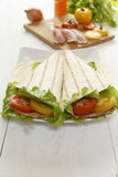 Tomatoes, bacon, salad and pita bread on an table Royalty Free Stock Images
