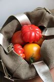 Tomatoes are in the bag. Red and yellow tomatoes are at the stylish handbag stock image