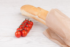 Tomatoes and baguette on a wooden table. Fresh cherry tomatoes on branch and  baguette  on a wooden table Stock Photography