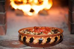 Tomatoes baked with mushrooms in a clay bowl with an ornament on the background of a wood-burning stove stock image