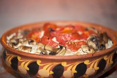 Tomatoes baked with mushrooms in a clay bowl with an ornament royalty free stock photography