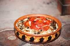 Tomatoes baked with mushrooms in a clay bowl with an ornament royalty free stock photo