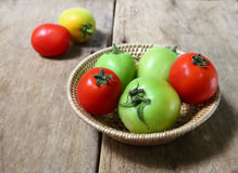 Tomatoes in bamboo basket on wooden background Stock Images