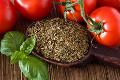 Tomatoes and basil. Tomatoes and dried basil on old wooden board Stock Photos
