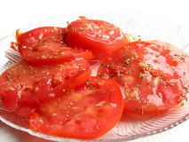 Tomatoes and Basil. Garden tomatoes garnished with dressing and basil Stock Image