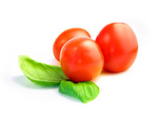 Tomatoes with basil. Three cherry tomatoes with two leafs of basil isolated on white Stock Photo