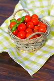Tomatoes with basil in basket Stock Photo