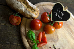 Tomatoes, basil and bread on a wooden table, Heart with text gut Royalty Free Stock Images