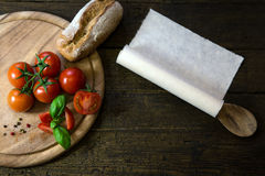 Tomatoes, basil and bread on a wooden table, scroll with copyspa Royalty Free Stock Images