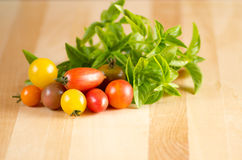 Tomatoes and basil on a cutting board Stock Photo