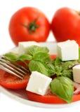 Tomatoes, basil and feta cheese salad. White background Stock Photo