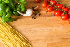 Tomatoes basil garlic allspice and pasta on the wooden table. Red small tomatoes green basil garlic allspice and pasta on the wooden table royalty free stock photo