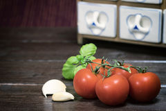 Tomatoes, basil and garlic lying on the wooden table. Vintage photo of cherry tomatoes, basil and garlic lying on the wooden table. Porcelain spice rack is in Stock Images