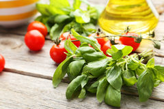 Tomatoes and basil leaves Stock Photography