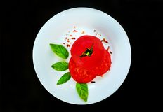Tomatoes and basil with specialties on a white round plate on a black background. stock photo