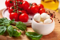 Tomatoes, basil, mozzarella cheese. Caprese salad ingredients. Cherry tomatoes, basil leaves, mozzarella cheese, olive oil and pepper mix on round wooden cutting Royalty Free Stock Photos