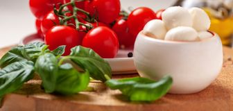 Tomatoes, basil, mozzarella cheese. Caprese salad ingredients. Cherry tomatoes, basil leaves, mozzarella cheese, olive oil and pepper mix on round wooden cutting Royalty Free Stock Photography