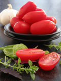 Tomatoes an basil. Plum tomatoes and basil , cut in half , on black plate and dark background Royalty Free Stock Photos