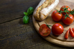 Tomatoes, basil and a rustic bread on a wooden table Stock Images