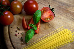 Tomatoes and basil with Spaghetti and pepper on a wooden plate Royalty Free Stock Photography