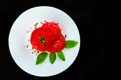 Tomatoes and basil with specialties on a white round plate on a black background. royalty free stock photography