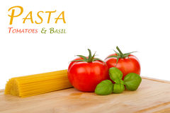 Tomatoes, basil and uncooked spaghetti Stock Photography
