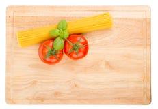 Tomatoes, basil and uncooked spaghetti Stock Photo