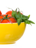 Tomatoes and basil in yellow bowl vertical half Stock Photos