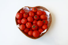 TOMATOES IN A BASKET WITH HEART SHAPED. Of ecological culture small tomatoes in a heart shaped basket, isolated on white background Stock Photography