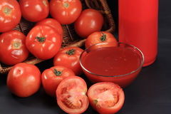 Tomatoes from basket and ketchup Stock Photo