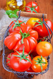 Tomatoes in a basket. On wooden table Royalty Free Stock Image
