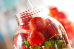 Tomatoes being swamped boiled water in process of Stock Image