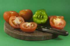 Tomatoes and bell peppers with knives Royalty Free Stock Photo