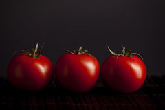Tomatoes on black background Stock Photography