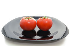 Tomatoes on a black plate Royalty Free Stock Photos