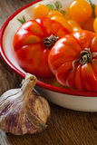 Tomatoes in a bowl and garlic Stock Photos