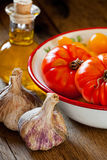 Tomatoes in a bowl, garlic and olive oil Royalty Free Stock Photography