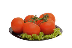 Tomatoes on a branch. Lying on a black plate with a green salad Royalty Free Stock Image